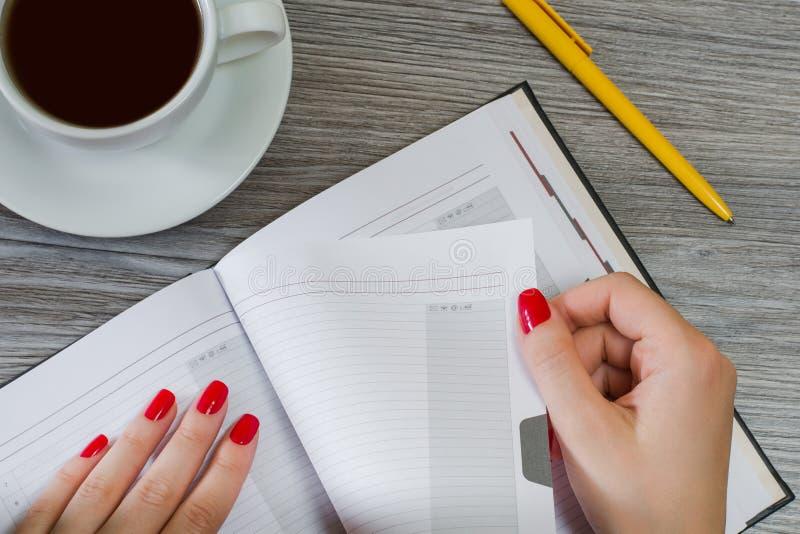 Il ` s della donna passa la presa della pagina dal suo blocco note Tazza di tè, penna fotografie stock