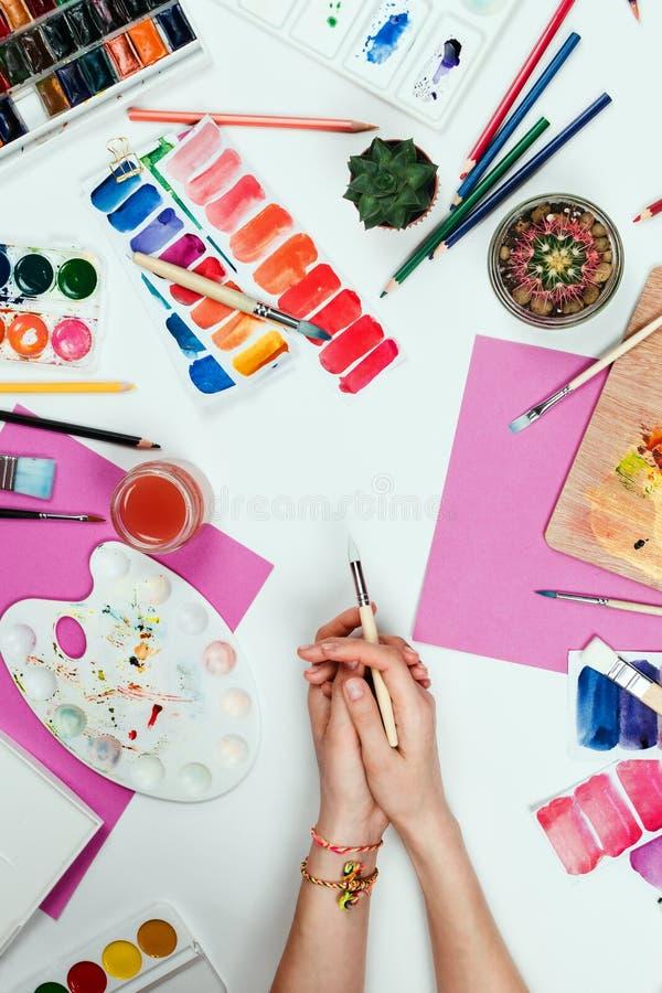 Il ` s della donna passa la spazzola della tenuta, i pallet, le matite, gli acquerelli, la carta colorata ed altri rifornimenti s fotografia stock libera da diritti