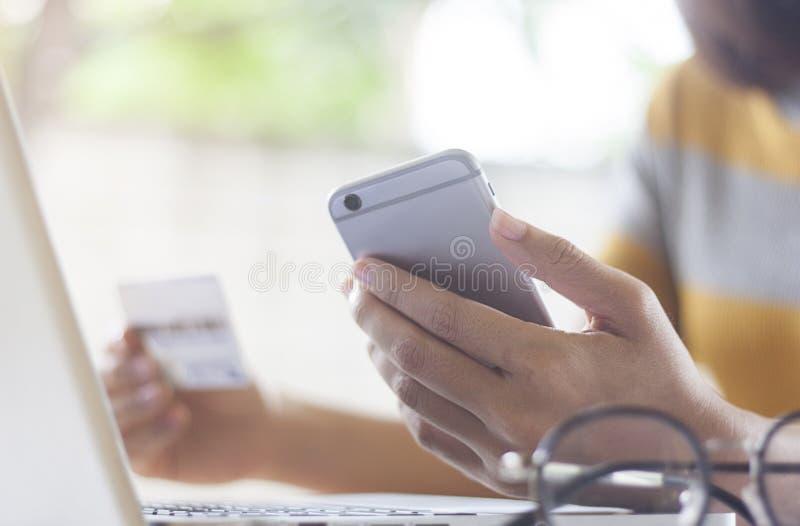Il ` s delle donne di affari passa la tenuta uno Smart Phone e della carta di credito fotografia stock
