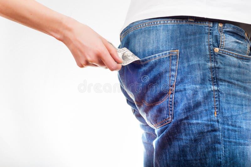 Il ` s delle donne passa tir indietroare la banconota in dollari dai jeans po del ` s degli uomini immagini stock