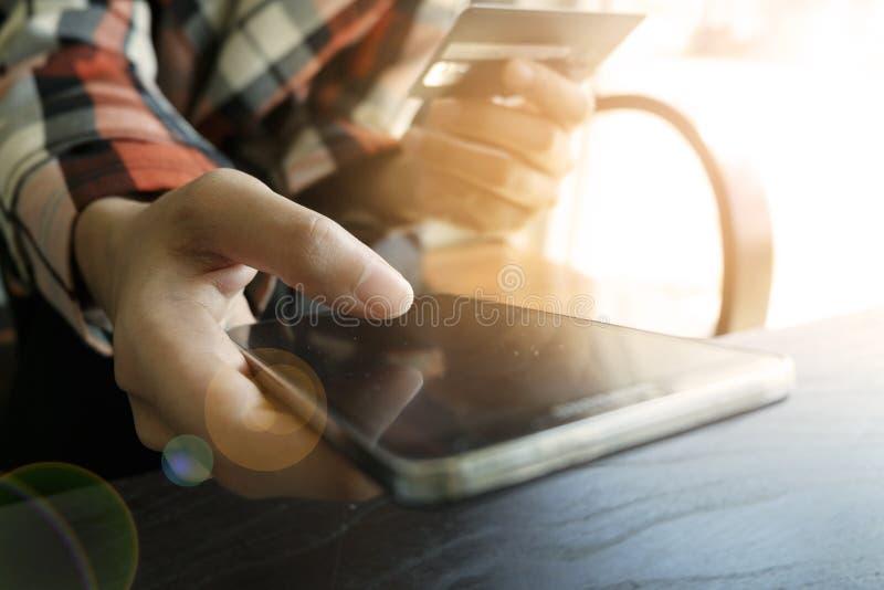 Il ` s di affari passa la tenuta della carta di credito e per mezzo dello Smart Phone per fotografia stock libera da diritti