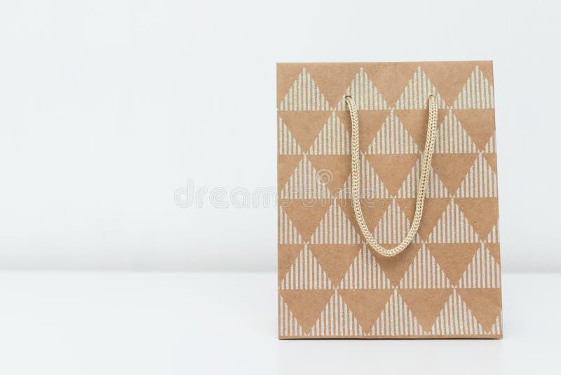 Il sacco di carta beige del cartone ha fatto del materiale riciclato di Kraft su fondo bianco con lo spazio della copia fotografia stock