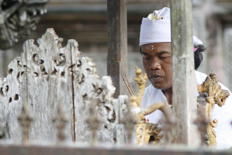 Il sacerdote indù prega in tempiale di Tirta Empul di Balinese fotografie stock libere da diritti