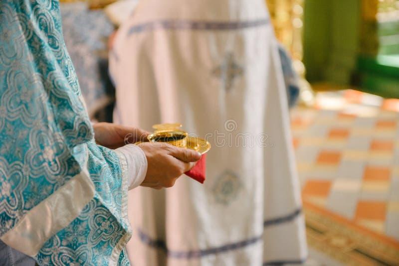 Il sacerdote nella chiesa tiene le fedi nuziali alle nozze immagini stock libere da diritti