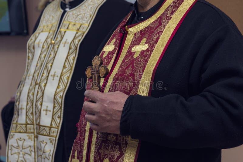 Il sacerdote ortodosso tiene un incrocio di legno in sua mano immagine stock