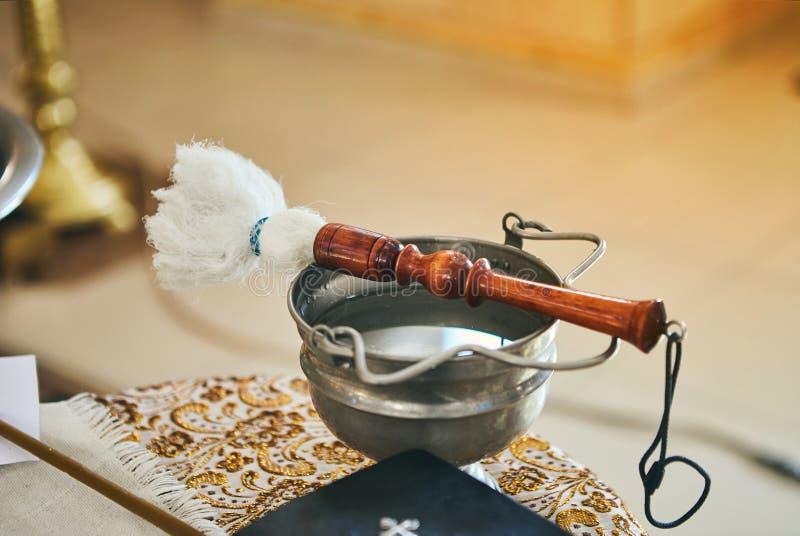 Il sacerdote ortodosso tiene una bibbia su una tavola con i vari oggetti stati necessari per il battesimo immagine stock libera da diritti