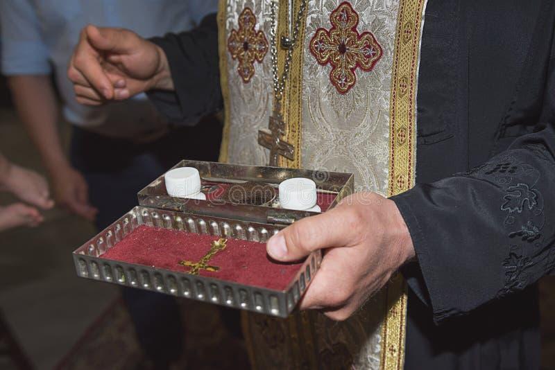 Il sacerdote tiene gli utensili della chiesa, le glande, cerimonia del battesimo dell'acqua, vari oggetti stati necessari per il  immagini stock