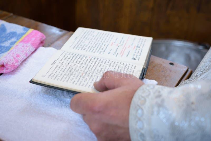 Il sacerdote tiene la bibbia all'altare, l'utensile della chiesa, la bibbia sulla tavola, cerimonia del battesimo di battesimo de fotografie stock