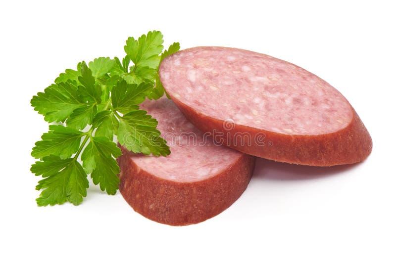 Il salame ha fumato le fette della salsiccia isolate su fondo bianco fotografia stock