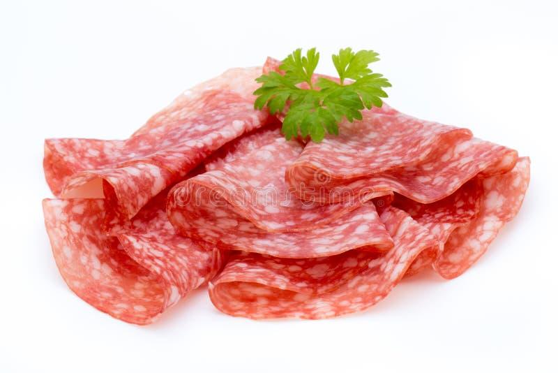 Il salame ha fumato le fette della salsiccia isolate sul ritaglio bianco del fondo fotografia stock libera da diritti
