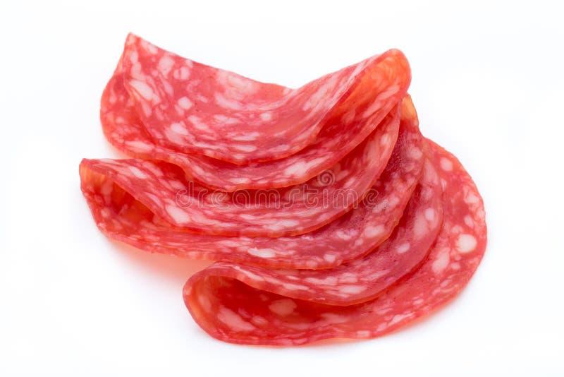 Il salame ha fumato le fette della salsiccia isolate sul ritaglio bianco del fondo immagini stock