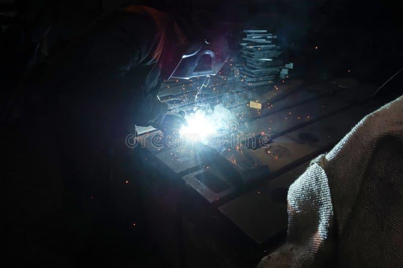 Il saldatore è impegnato nel realizzare il lavoro di saldatura con l'aiuto della saldatura ad arco elettrico nel suo luogo di lav immagini stock