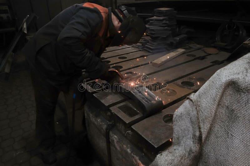 Il saldatore è impegnato nel realizzare il lavoro di saldatura con l'aiuto della saldatura ad arco elettrico nel suo luogo di lav fotografia stock