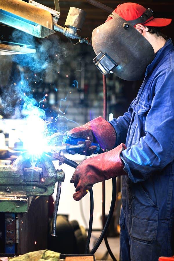 Il saldatore fa parte del metallo della saldatura in garage con la maschera protettiva, saldatore d'acciaio industriale fotografia stock libera da diritti