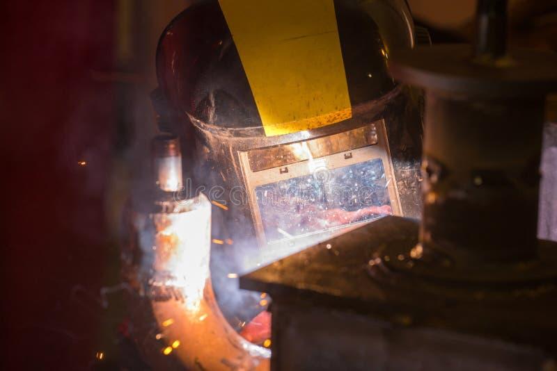 Il saldatore funzionante in una maschera con vetro collega il metallo da weldin fotografia stock