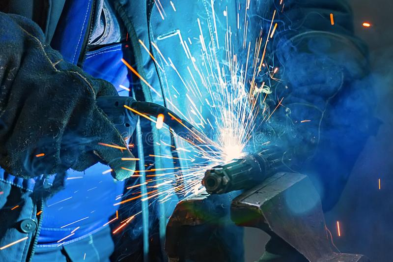 Il saldatore in guanti salda una parte di metallo nella fabbrica 8 fotografia stock