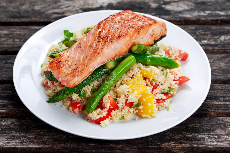 Il salmone fritto con asparago e lo zucchino teneri è servito su cuscus misto con il pomodoro dolce, salsa gialla del pepe fotografia stock libera da diritti