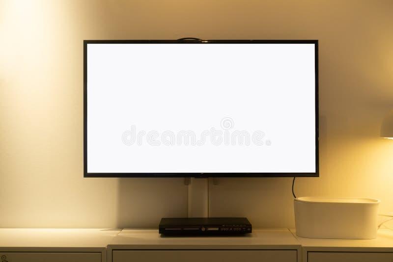 Il salone ha condotto lo schermo in bianco TV sul muro di cemento con la tavola ed il lettore multimediale di legno Schermo in bi immagini stock libere da diritti