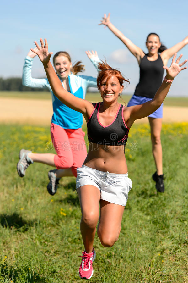 Il salto allegro degli amici gode del funzionamento di sport dell'estate immagine stock