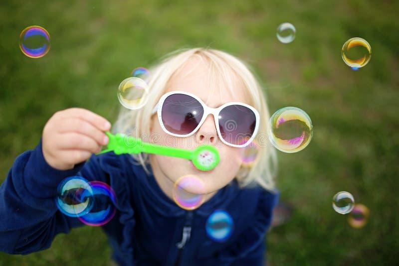 Il salto del bambino della bambina bolle fuori un giorno di estate fotografia stock libera da diritti