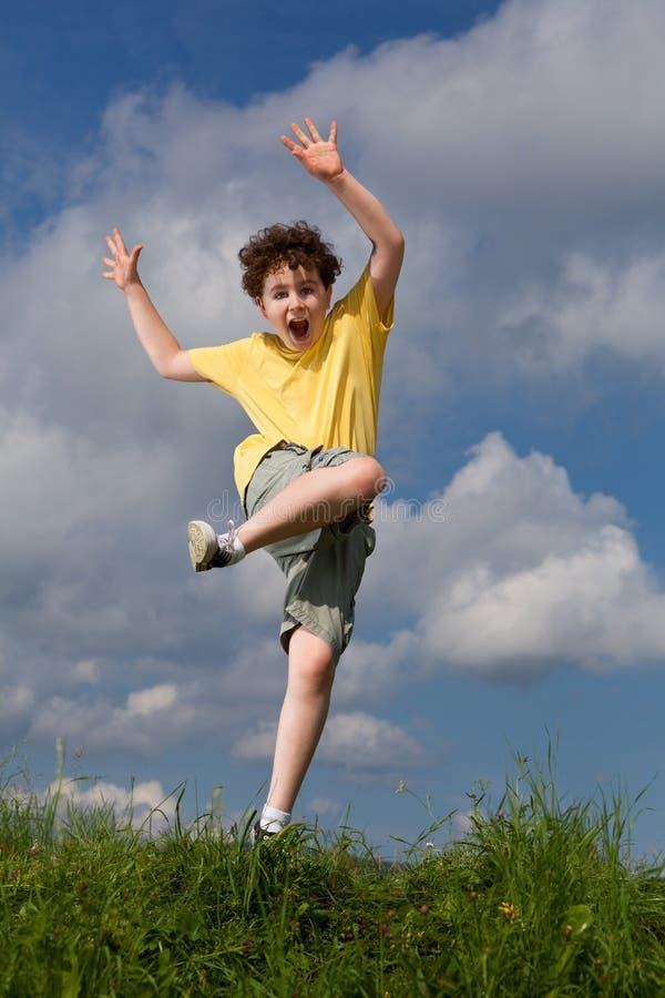 Il salto del ragazzo esterno fotografia stock