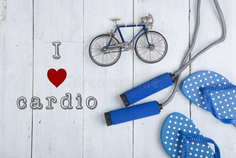 Il salto/salto della corda con le maniglie blu, i Flip-flop, modello della bicicletta su fondo di legno bianco con testo amo card fotografia stock libera da diritti