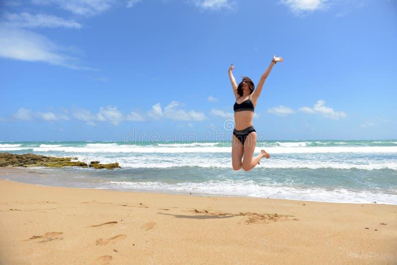 Il salto della donna della gioia nella spiaggia fotografia stock libera da diritti