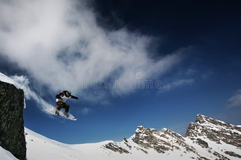 Il salto dello Snowboarder fotografia stock