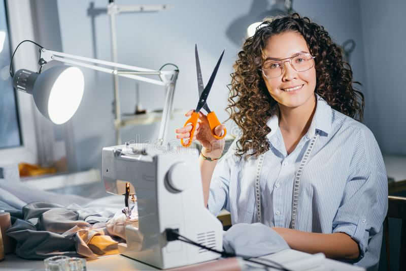 Il sarto da donna felice sta tenendo le forbici arancio per cominciare a cucire il processo fotografie stock