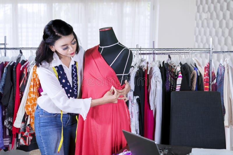 Il sarto da donna femminile regola un vestito su un manichino immagini stock
