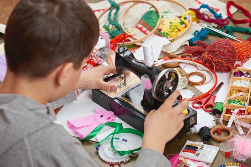 Il sarto del ragazzo impara concetto fatto a mano e di artigianato cucire, di formazione sul lavoro, immagini stock libere da diritti