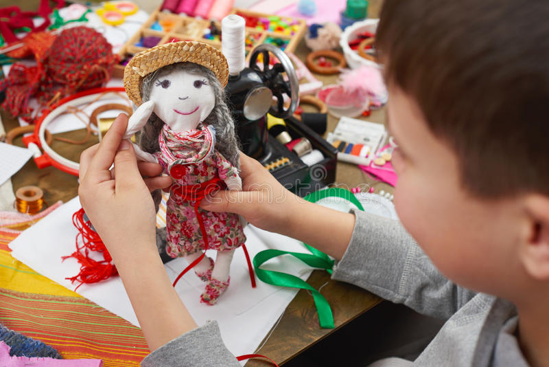 Il sarto del ragazzo impara cucire, vestirsi per il concetto fatto a mano e dell'artigianato della bambola, immagine stock libera da diritti