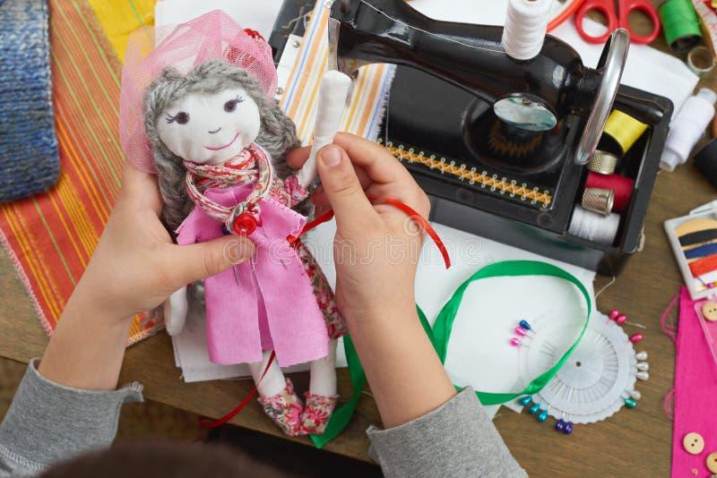 Il sarto del ragazzo impara cucire, vestirsi per il concetto fatto a mano e dell'artigianato della bambola, fotografia stock libera da diritti