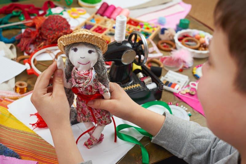 Il sarto del ragazzo impara cucire, vestirsi per il concetto fatto a mano e dell'artigianato della bambola, immagini stock