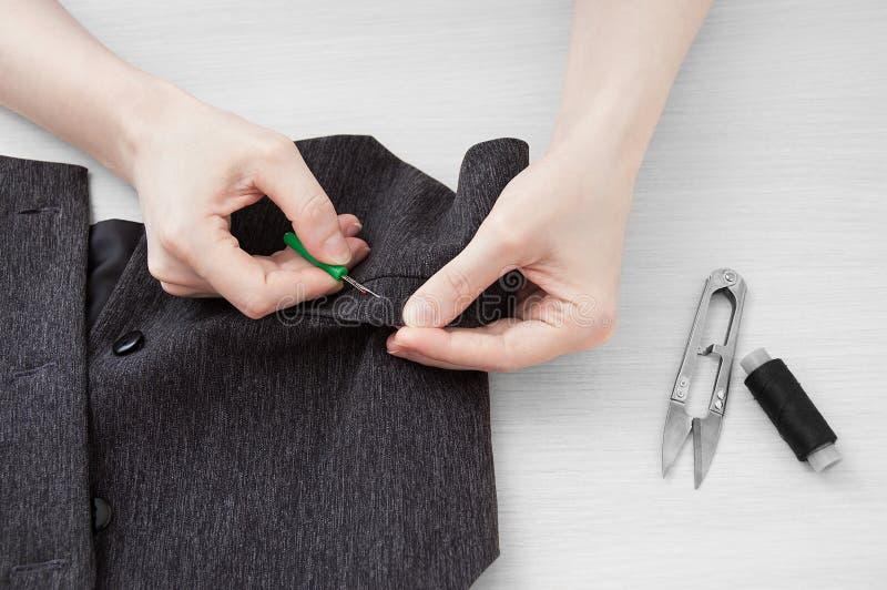 Il sarto della ragazza strappa il filo su un panciotto grigio immagini stock