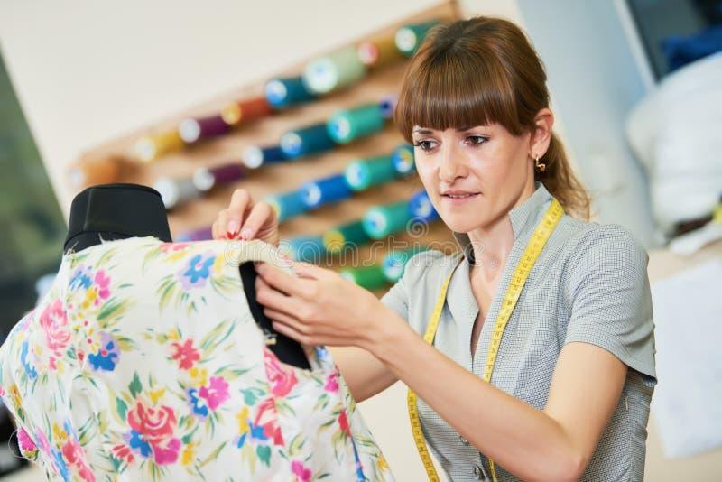 Il sarto femminile lavora con il vestito del rivestimento fotografia stock libera da diritti