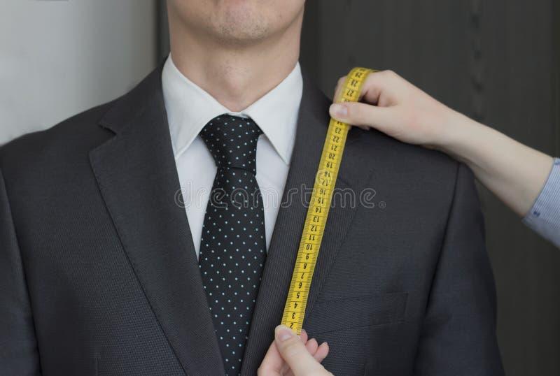 Il sarto prende le misure dal vestito, fondo bianco, isolato immagini stock