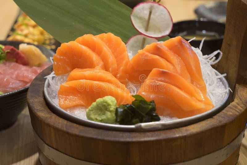 Il sashimi crudo di color salmone decora su ghiaccio e sul piatto di legno del canestro nello stile del ristorante giapponese Fuo fotografia stock