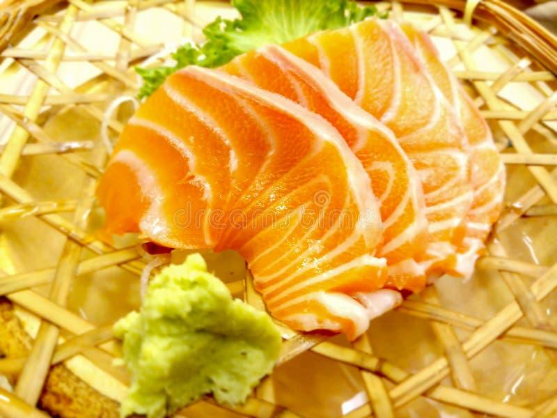 Il sashimi fresco di color salmone con wasabi e lattuga è servito in un piatto tessuto del rattan fotografia stock libera da diritti