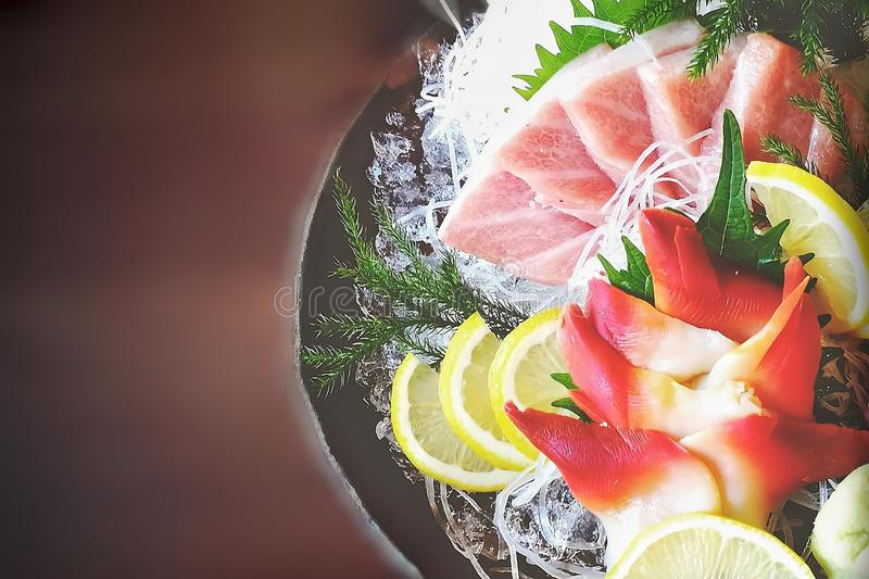 Il sashimi giapponese fresco in piatto nero ha messo la superficie di legno sopra vaga immagini stock