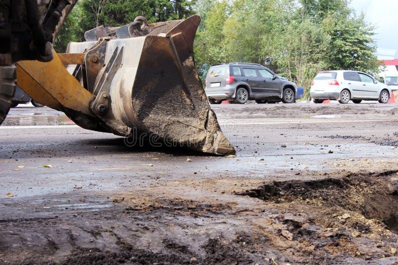 il secchio del trattore si trova sulla strada asfaltata quando scava il suolo sotto durante la riparazione della strada immagine stock