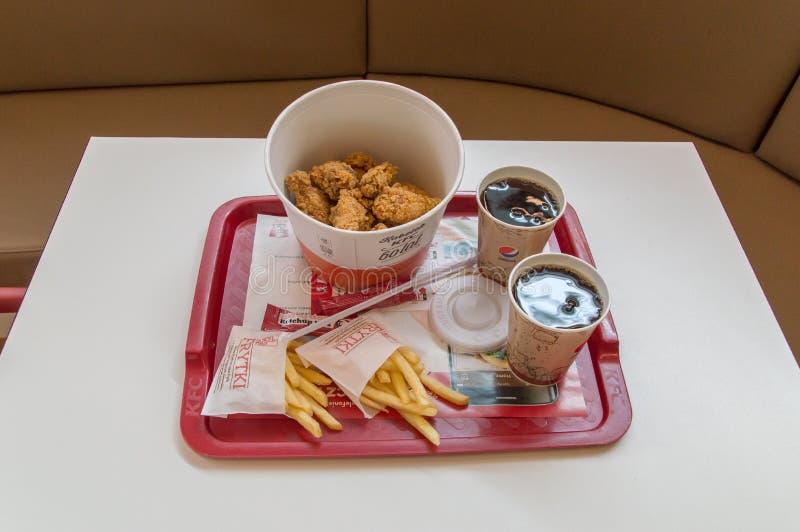Il secchio delle ali calde del pollo fritto, le patate fritte, due tazze con pepsi-cola per la bevanda ed il ketchup in KFC Kentu immagine stock libera da diritti