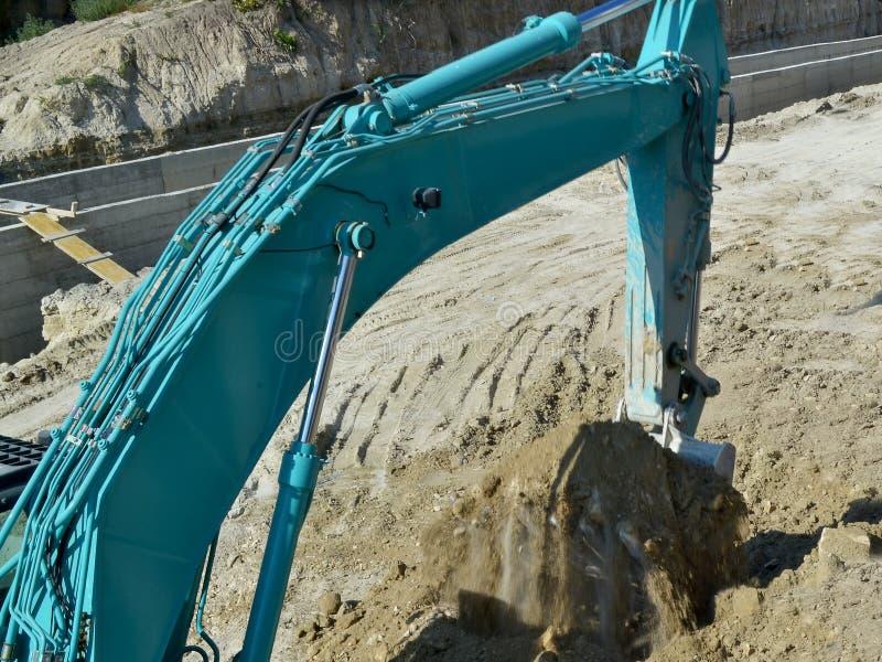 Il secchio di un escavatore blu ha scavato appena sulla terra al sito dei lavori stradali fotografia stock