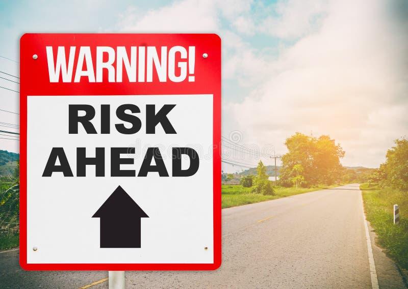 Il segnale di pericolo sulla strada avanti dice il rischio avanti fotografia stock