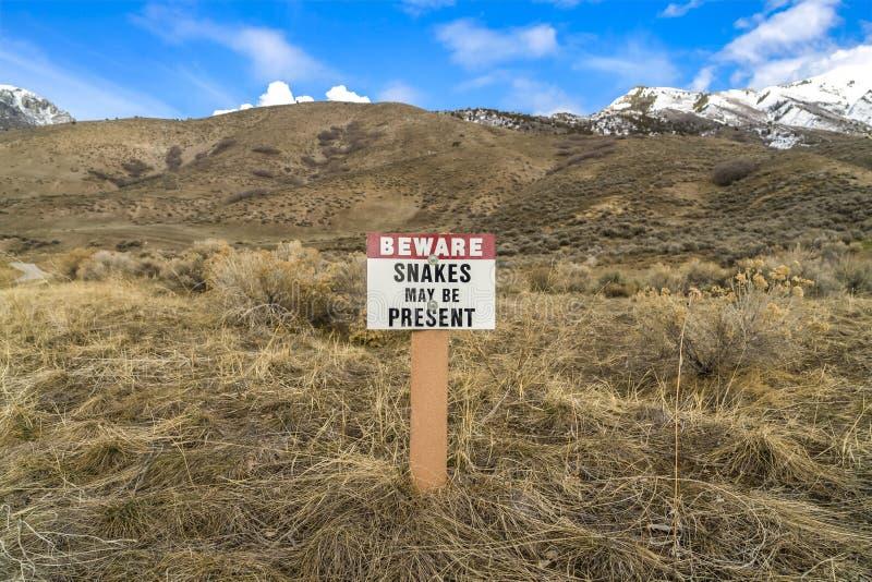 Il segno che legge si guarda dai serpenti può essere presente su una montagna erbosa immagini stock libere da diritti