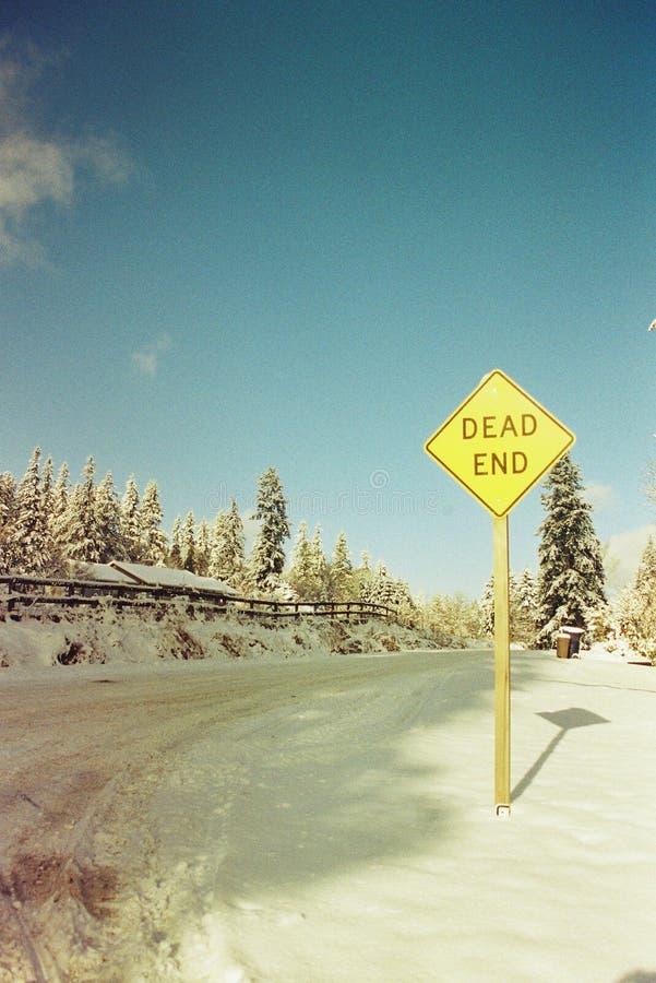 Il segno del vicolo cieco accanto alla strada è coperto di neve fotografia stock