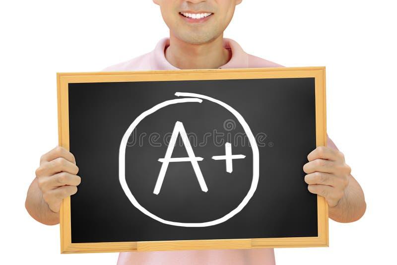 Il segno di A+ sulla lavagna ha tenuto dall'uomo sorridente fotografia stock