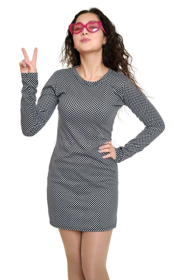 Il segno di vittoria di manifestazione del ritratto di bellezza della ragazza, vestito a quadretti in bianco e nero, occhiali da  fotografie stock