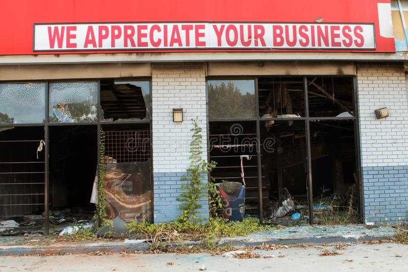 Il segno ironico si siede in cima alla piccola impresa bruciata e vandalizzata fotografia stock