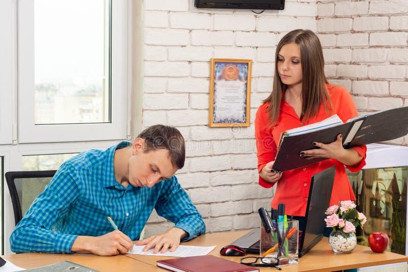 Il segretario firma i documenti con la testa fotografia stock